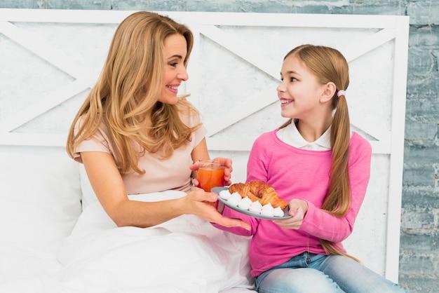 ベッドの中で母親に皿の上のクロワッサンを与える娘
