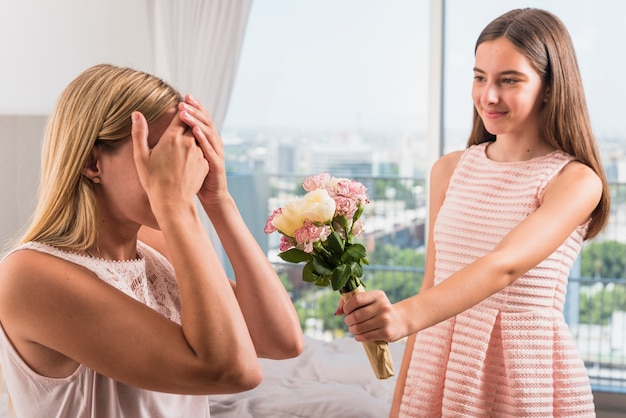 Daughter giving flowers bouquet to mother