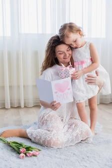 Daughter giving gift box to her mother while reading greeting card