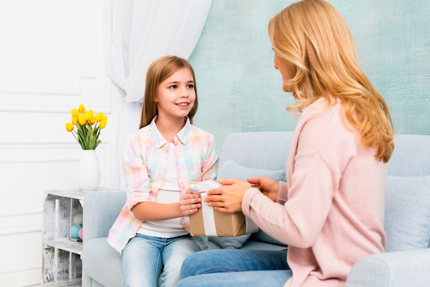 Daughter giving gift box for mom sitting on couch