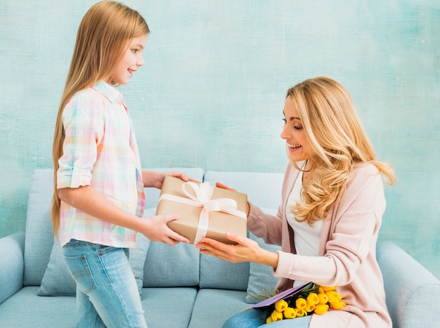 Daughter giving gift box for mother