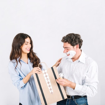 Daughter giving gift to shaving father