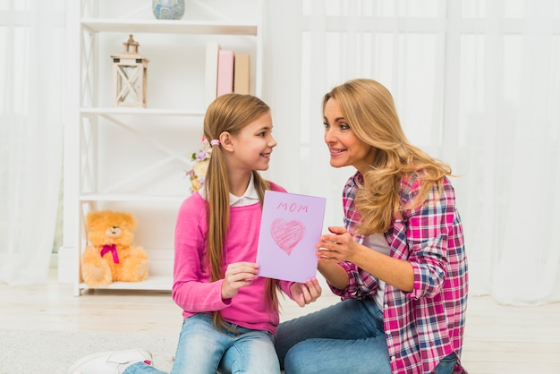 Daughter giving greeting card to mother