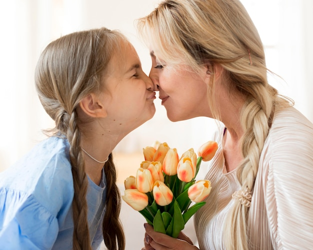 Daughter giving mother bouquet of flowers