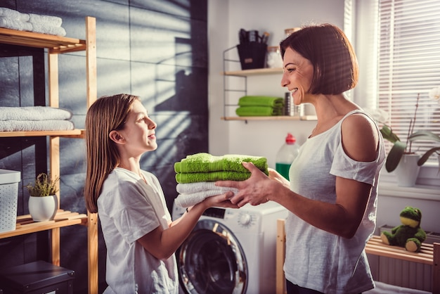 Daughter giving mother green folded towels