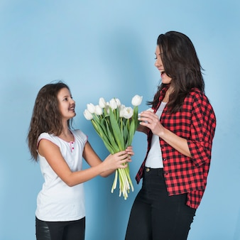 Daughter giving tulips to amazed mother