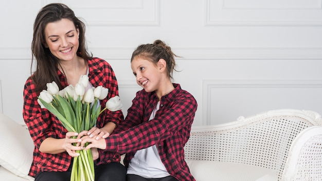 Daughter giving white tulips to mother on couch
