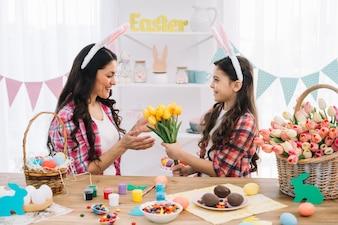 自宅でイースターの日の準備と彼女の母親に黄色い花チューリップを与える娘
