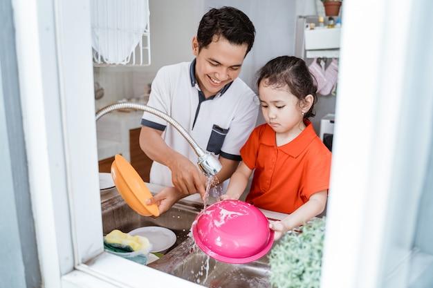 娘が父親が皿を洗うのを手伝う