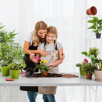 Daughter helping mom in greenhouse