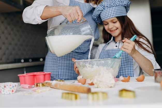 Daughter and her mother cooking a cake. mother pours milk and girl smiling