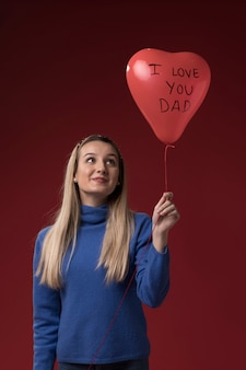 Daughter holding a balloon for her father