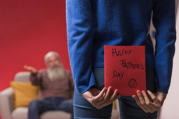 Figlia che tiene una cartolina d'auguri di festa del papà
