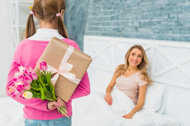 Daughter holding gift and tulips for mother in bed