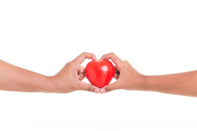 Daughter holding and giving red heart to her mother hand isolated on white