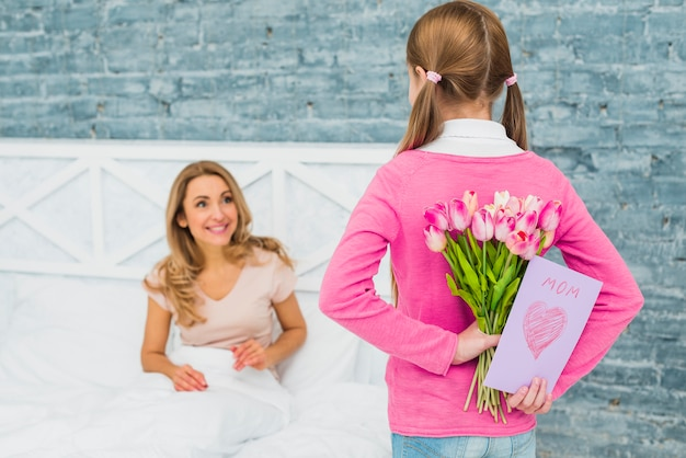 Daughter holding greeting card and tulips for mother in bed