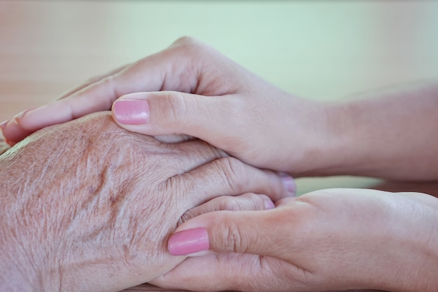 A daughter holding her mother's hand on mother's day