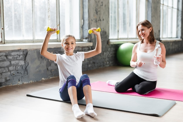 Daughter holding weights while mom watching