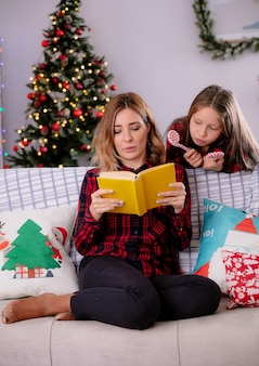 娘はキャンディケインを持って、ソファに座って家でクリスマスの時間を楽しんでいる本を読んでいる母親を見ています
