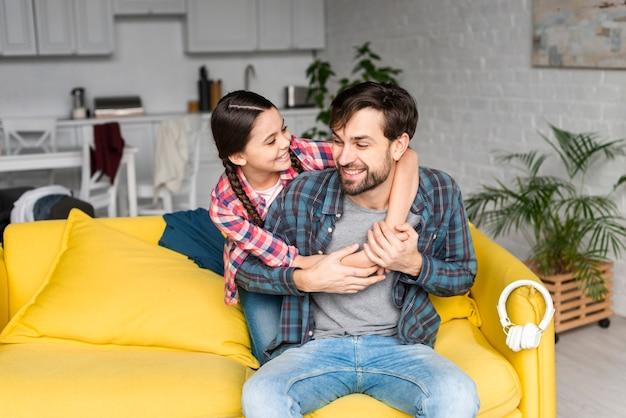 Дочь обнимает отца в гостиной