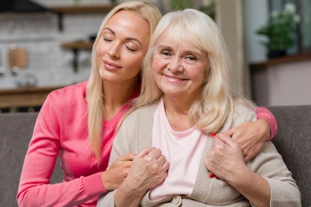 딸이 그녀의 어머니를 포옹하고 소파에 앉아
