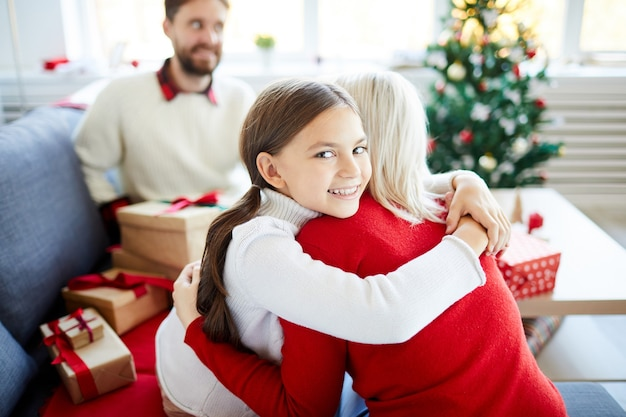 Figlia che abbraccia sua madre il giorno di natale