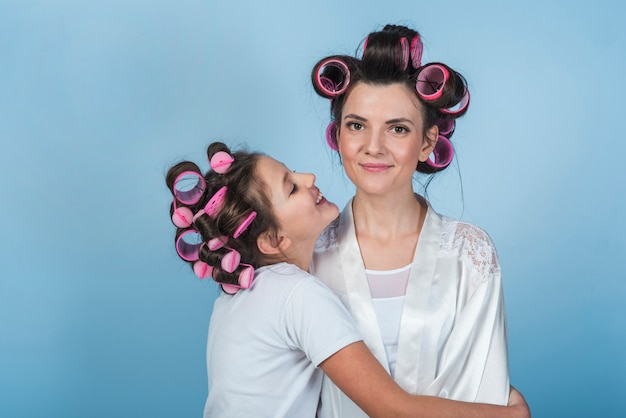 Daughter hugging mother in curlers and bathrobe