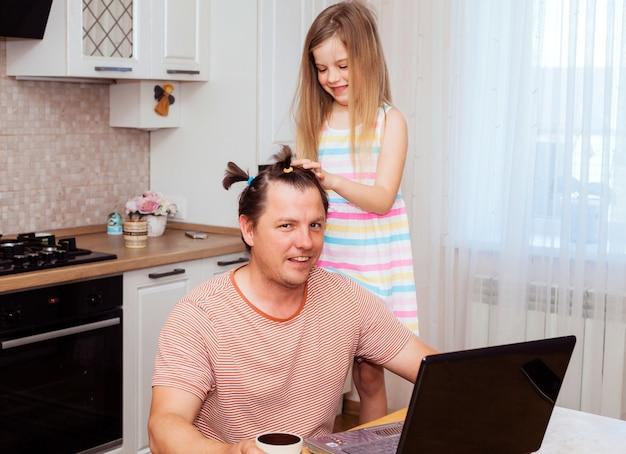 Дочь обнимает папу. молодой папа работает с ноутбуком, маленькая дочка обнимает его сзади