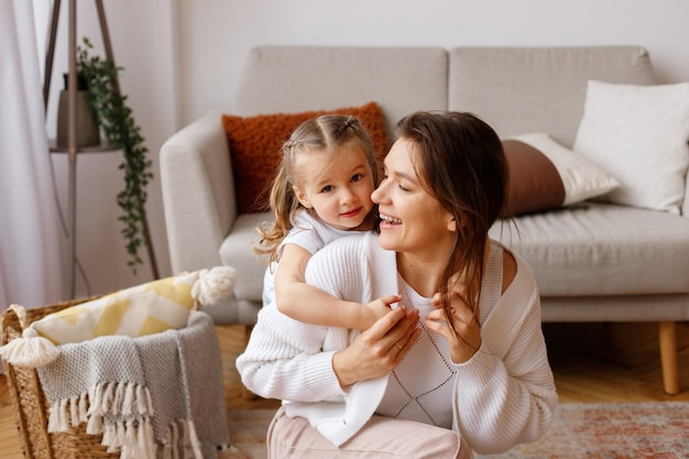 딸은 휴일에 거실에서 그녀의 어머니를 안아