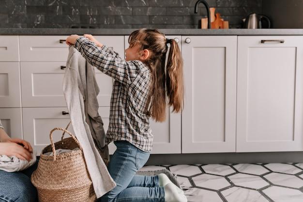 ジーンズとシャツを着た娘は、お母さんを助け、バスケットから汚れた服を引き出します。