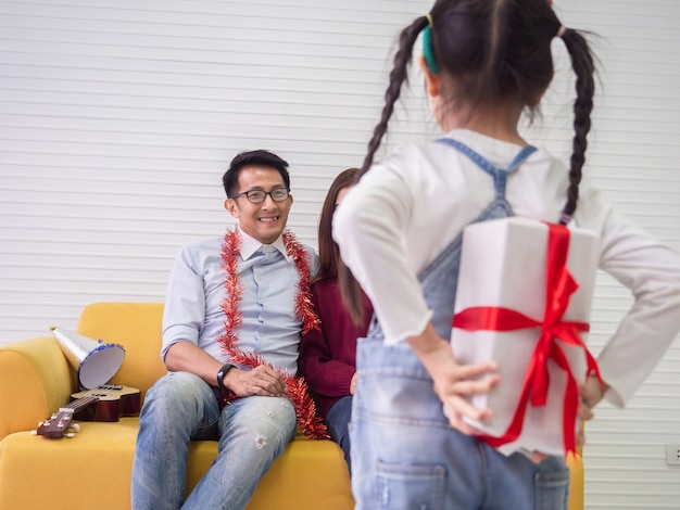 Daughter is giving a gift to mother and father, family concept