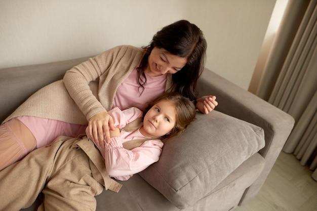 Дочь обижается на маму. мама и дочка лежат на диване и возятся или дурачатся