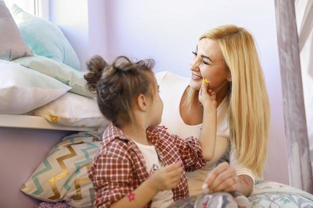 娘は明るい部屋で母親の顔にステッカーを貼っている