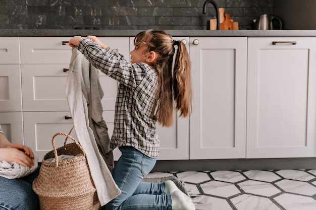 Daughter in jeans and shirt helps mom and pulls out dirty clothes from basket.