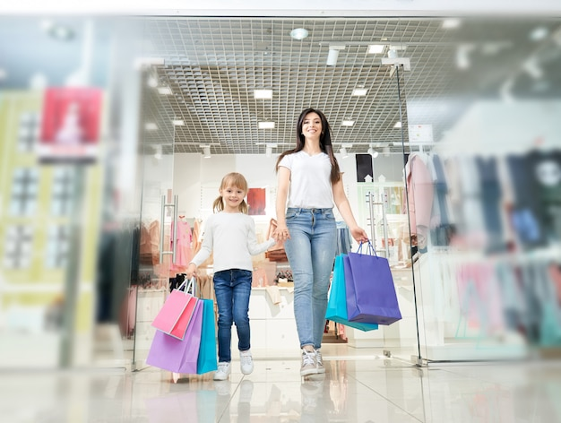 Daughter keeping hand of mother and going out from store