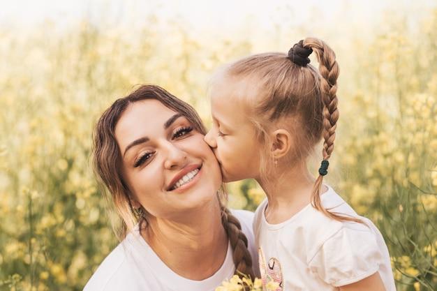 Летом дочь целует маму на природе. день матери