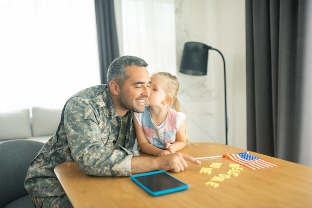 娘が父にキスします。兵役後に帰宅する父親にキスする金髪の娘