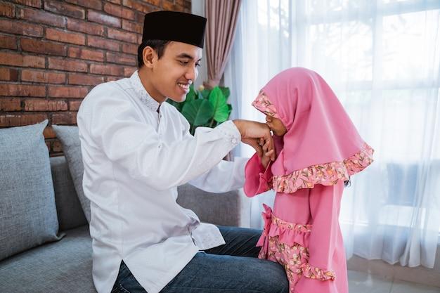 イードムバラクで父親に手をキスする娘