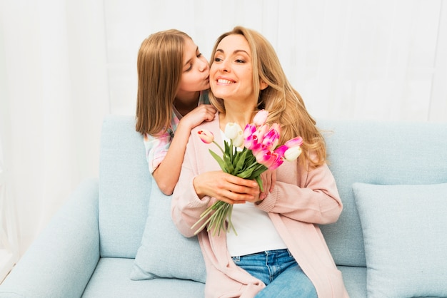 Daughter kissing happy mother with flowers