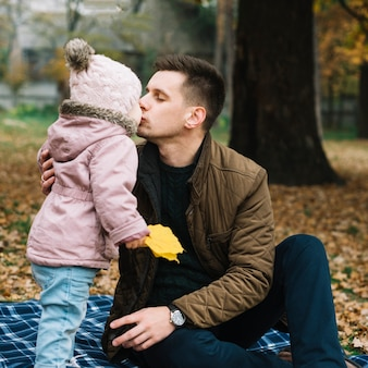 Daughter kissing her dad in autumn woods