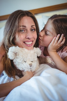 Daughter kissing mother on bed