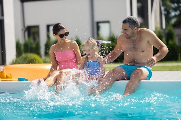 Дочь смеется. веселая милая дочь смеется, брызгая водой, сидя рядом с родителями