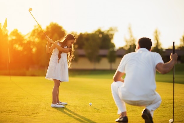 Daughter learns to take golf shot happy family.