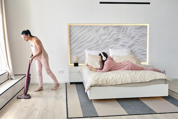 Дочь лежит на животе в постели и слушает музыку со смартфона в наушниках, пока мама пылесосит пол в спальне.