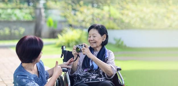 裏庭で年配の母親の世話をする娘