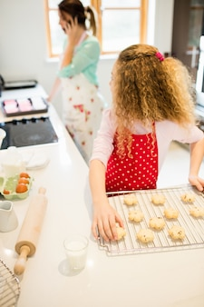 Daughter looking at her mother while taking cookies in kitchen
