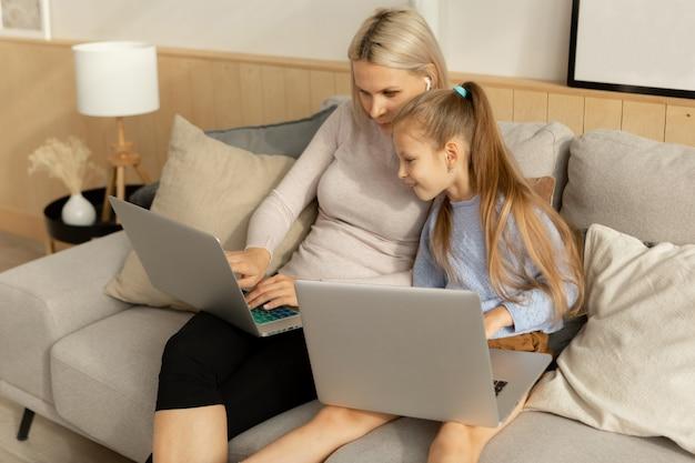 그녀의 어머니의 노트북 화면을보고 딸입니다. 부모와 함께 공부하는 아이.