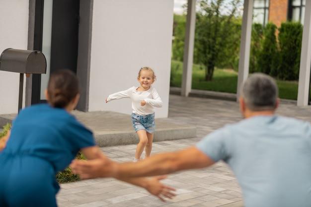 Дочь знакомится с родителями. веселая милая маленькая дочь встречает родителей, возвращающихся с работы