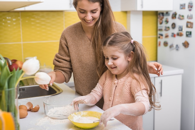 Daughter mixing flour with eggs in bowl