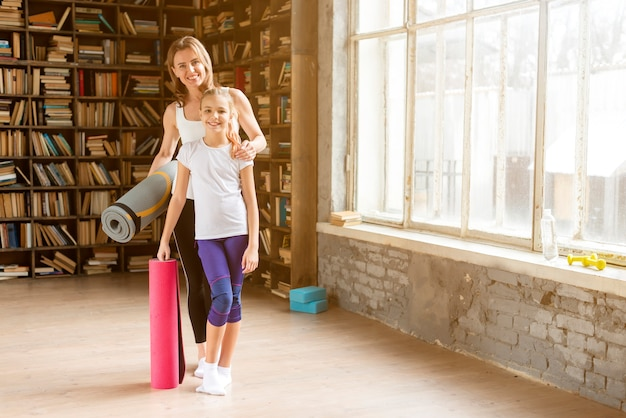 Daughter and mom holding yoga mats